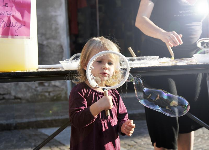 Portrait of child girl blowing big soap bubble. Real shot stock photography