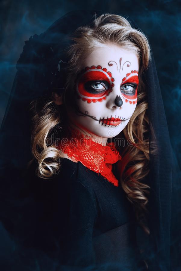 Make-up of calavera catrina. Portrait of a child girl in a costume of Calavera Catrina over black background. Little girl with sugar skull makeup. Halloween stock photo