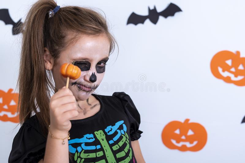 Portrait of a child girl with sugar skull makeup in a costume of skeleton over white background with bats and pumpkin. Portrait of a child girl in a costume of stock photo