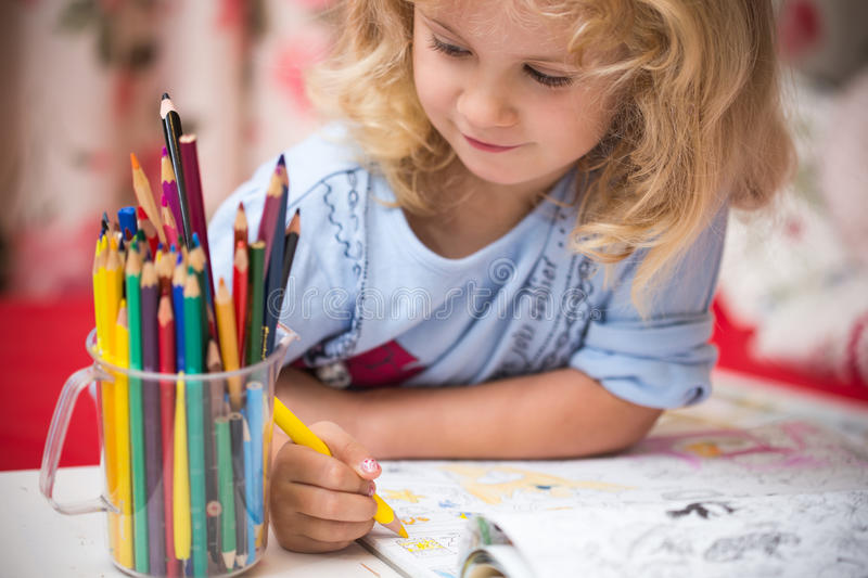 Portrait of child girl drawing with pencils stock photography