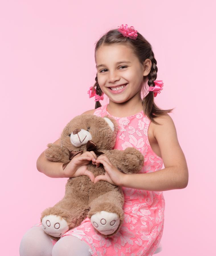 Portrait of Child Girl Hugging Her Soft Toy Bear on Pink Backdrop and Doing Heart Gesture. Portrait of Child Girl Hugging Her Soft Toy Bear on Pink Background royalty free stock photography