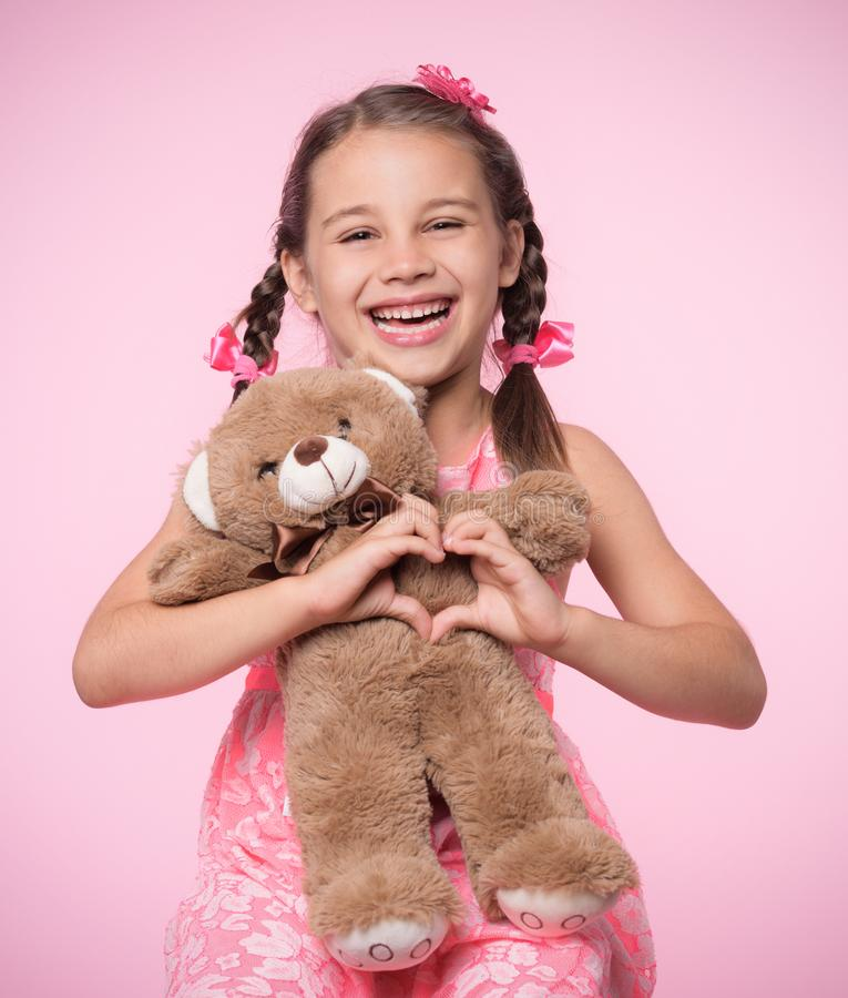 Portrait of Child Girl Hugging Her Soft Toy Bear on Pink Backdrop and Doing Heart Gesture. Portrait of Child Girl Hugging Her Soft Toy Bear on Pink Background stock images