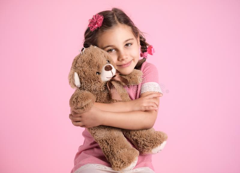 Portrait of Child Girl Hugging Her Soft Toy Bear on Pink Backdrop stock image