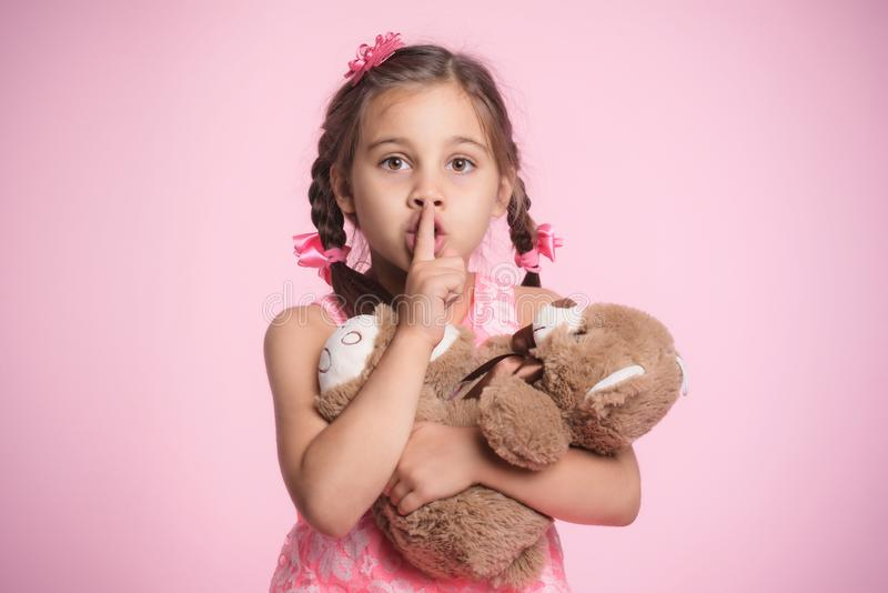 Portrait of Child Girl Hugging Her Soft Toy Bear on Pink Background and Doing Gesture to Silence stock photo