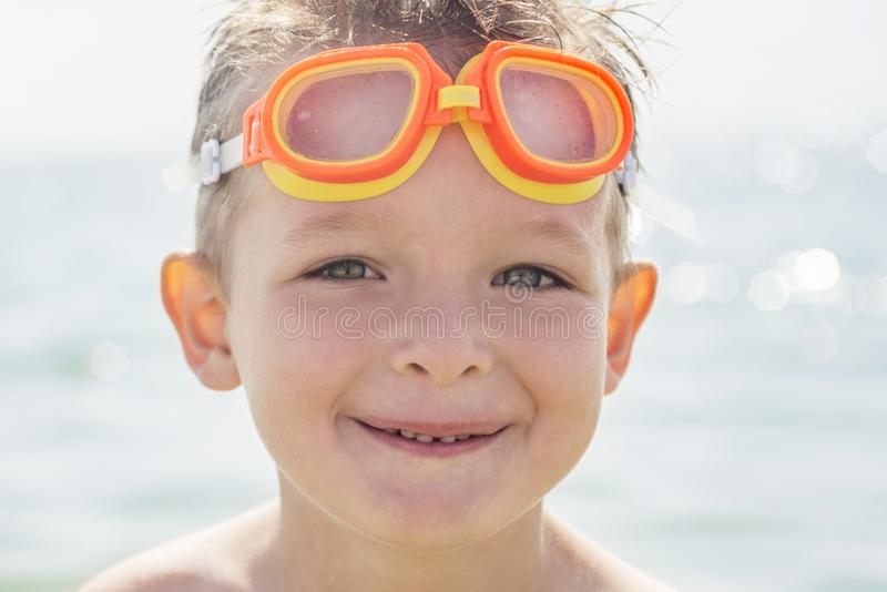 Portrait of a child in glasses for swimming against the sea. Kid in spectacles for swimming at the sea stock image