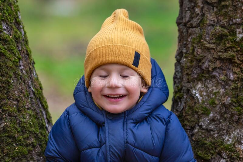 Portrait of a child outdoors. Happy little boy makes a wish royalty free stock image
