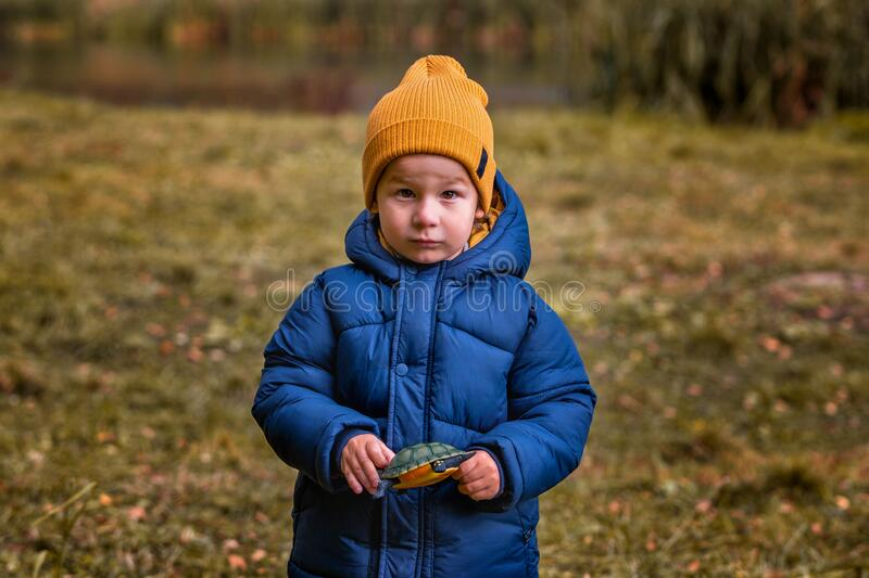 Portrait of a child outdoors. Serious boy with a toy in his hand stock photography