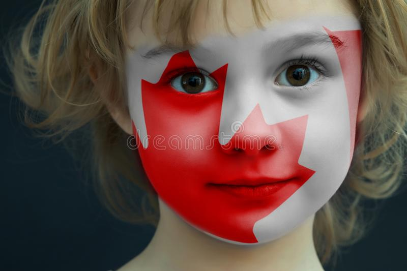 Child with a painted flag of Canada stock photo