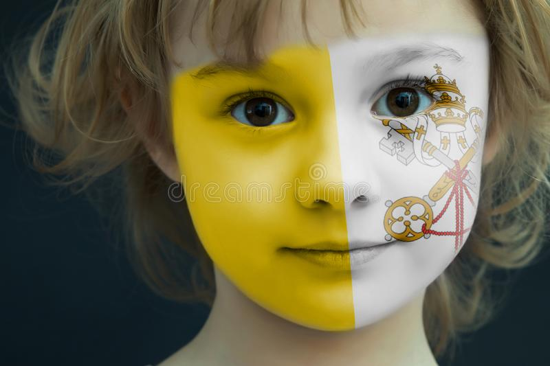 Portrait of a child with a painted Vatican City flag. On her face, closeup stock photos