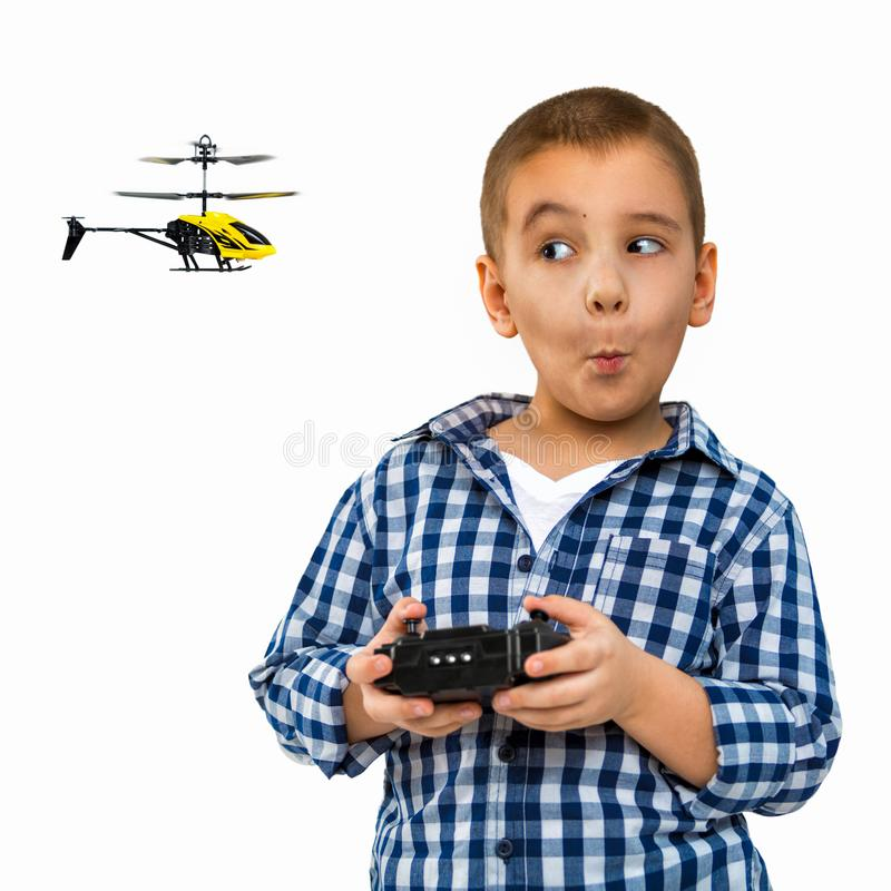 Portrait of a child with a toy. A little boy drives a helicopter. Photo indoors on a white background stock photos