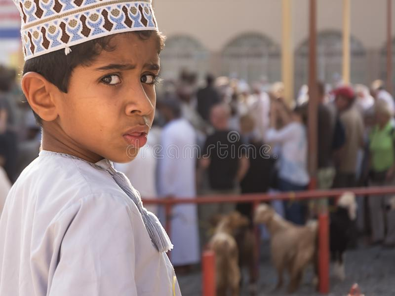 Portrait of child turning around surprised by the camera at the Friday animal market in Nizwa royalty free stock photos