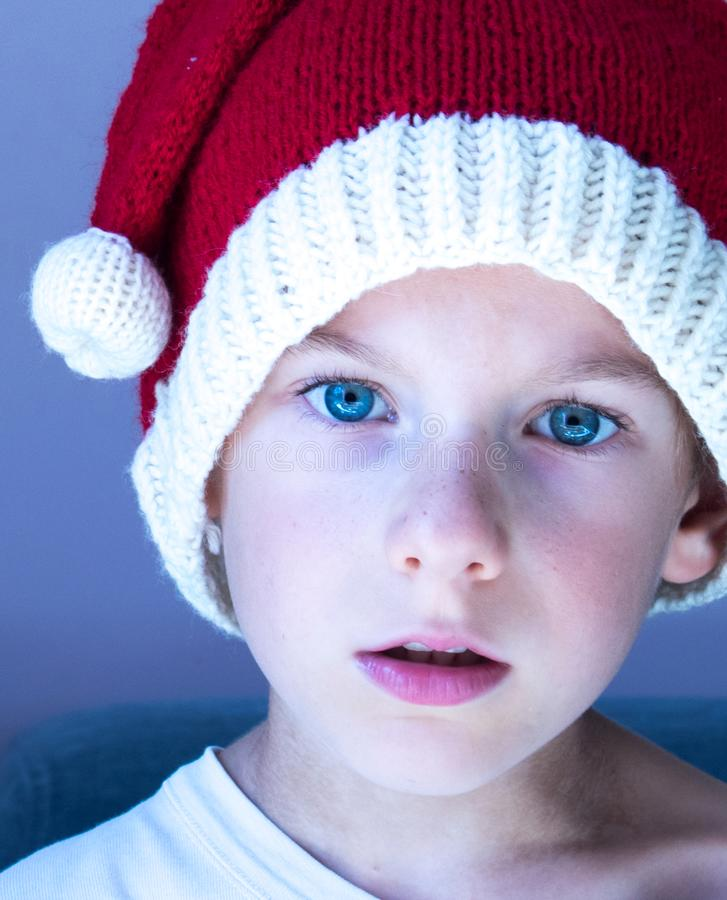 A portrait of a child wearing a knitted Santa hat. Xmas design. Enchantment, surprise, astonishment, wonder expression royalty free stock photos