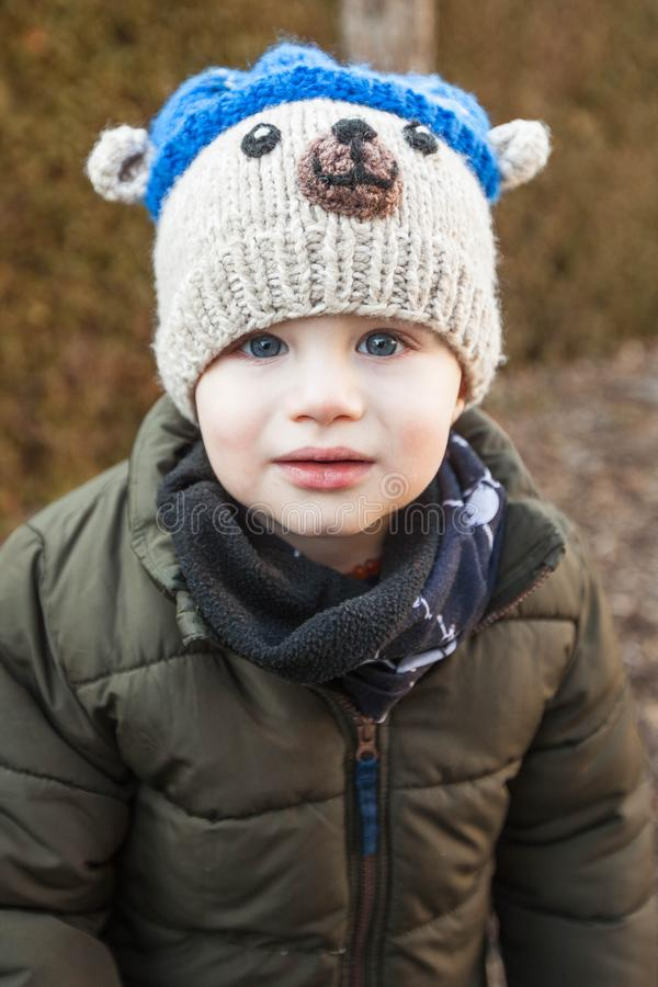 Portrait of child wearing scarf and bear hood, winter royalty free stock image