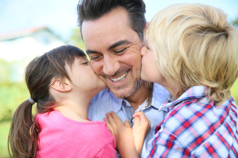 Portrait of children kisseng their happy father stock images