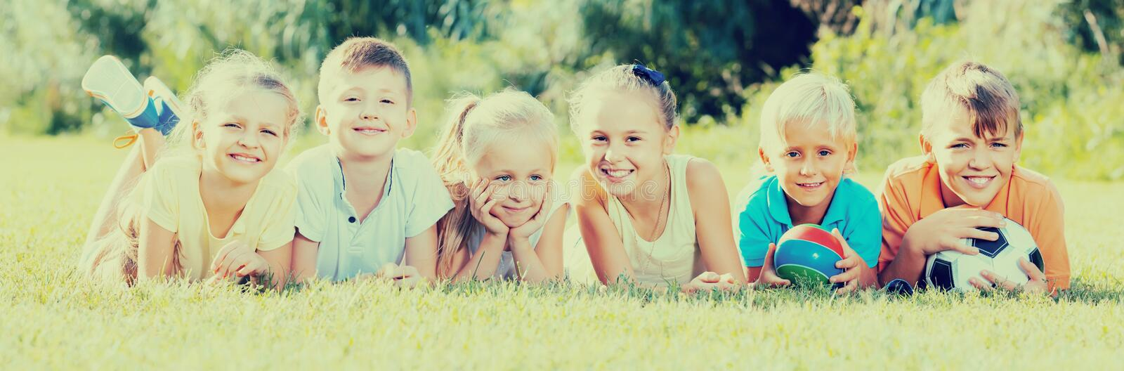 Portrait of children lying on grass in park and looking happy stock photo