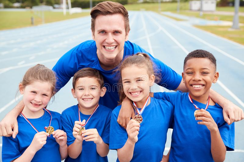 Portrait Of Children With Male Coach Showing Off Winners Medals On Sports Day stock photo
