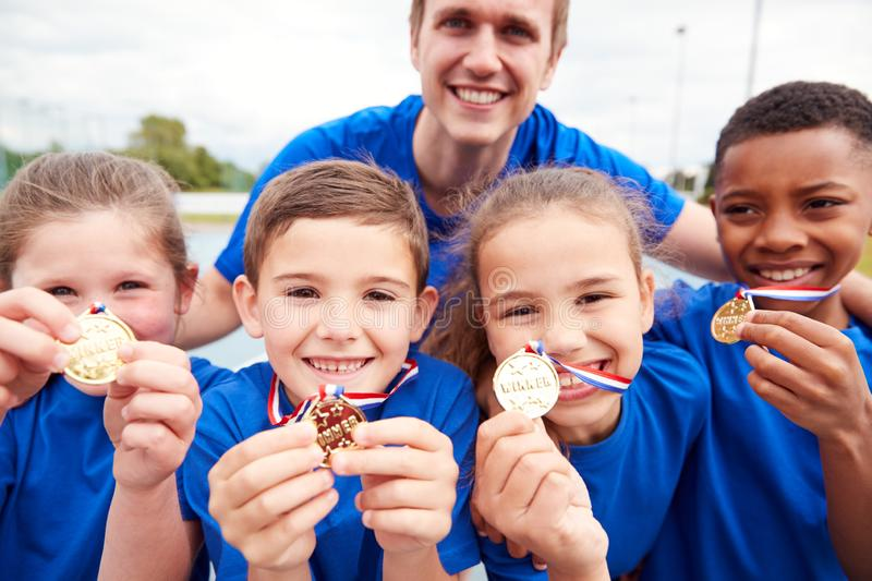 Portrait Of Children With Male Coach Showing Off Winners Medals On Sports Day royalty free stock images