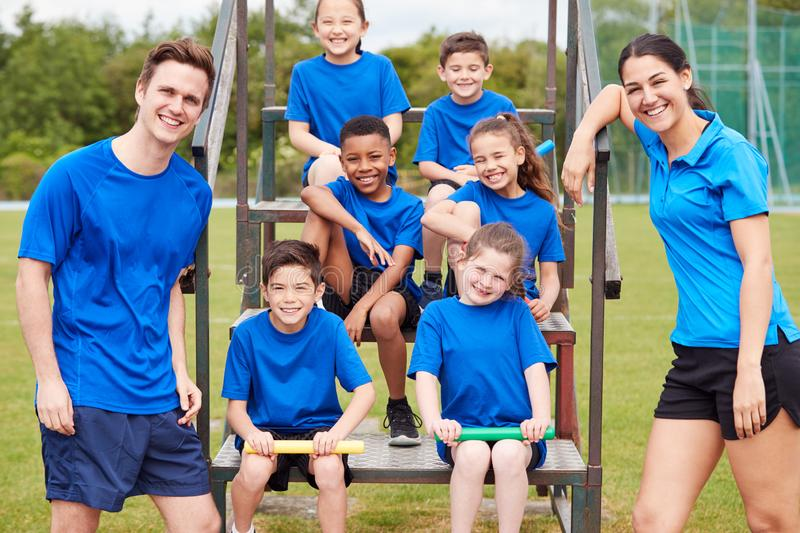 Portrait Of Children With Male And Female Coaches Preparing For Relay Race On Sports Day stock photo