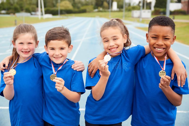 Portrait Of Children Showing Off Winners Medals On Sports Day royalty free stock photo