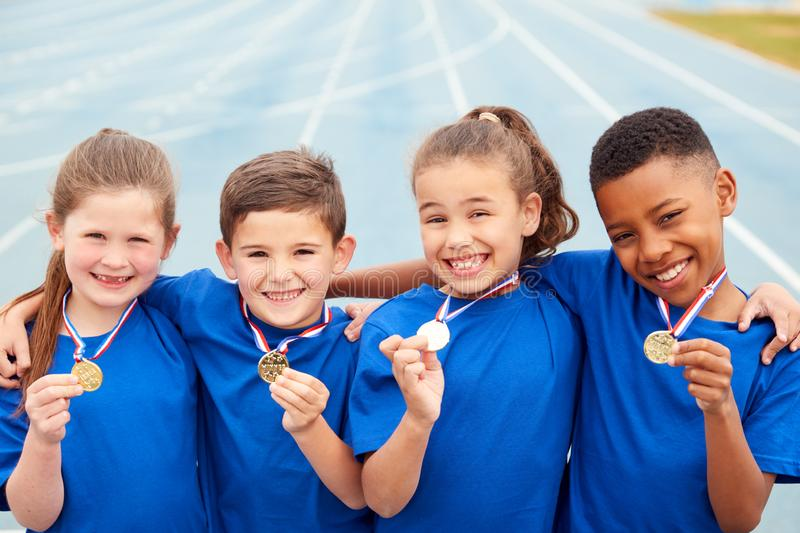 Portrait Of Children Showing Off Winners Medals On Sports Day royalty free stock image