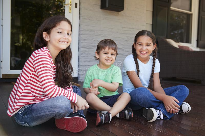 Portrait Of Children Sitting On Porch Of House Together royalty free stock photography