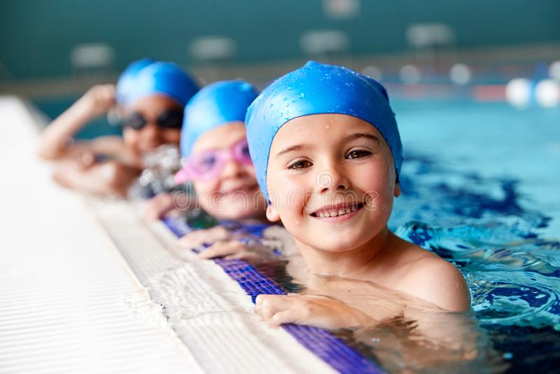 Portrait Of Children In Water At Edge Of Pool Waiting For Swimming Lesson stock images