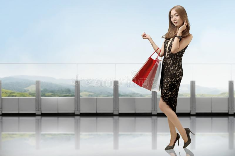 Portrait of chinese woman in black dress holding shopping bags stock photo