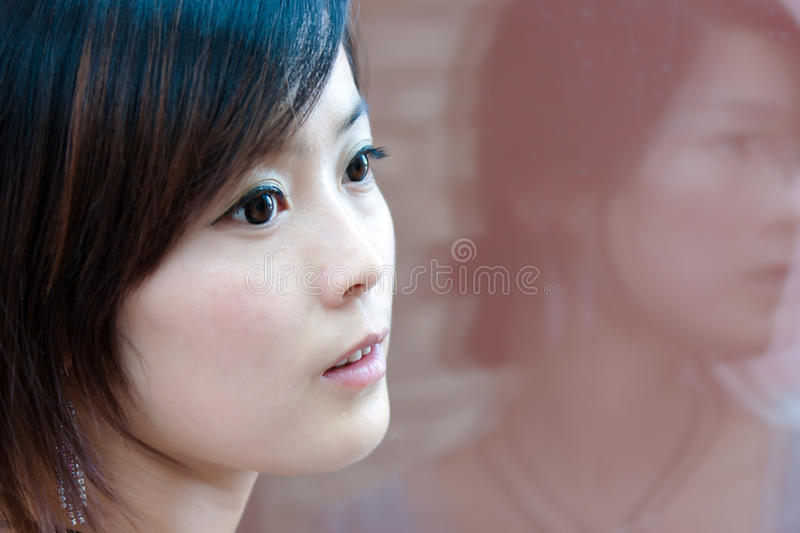 Portrait of the city girl reflection in glass wall royalty free stock image
