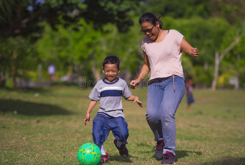Happy Asian Indonesian mother playing football with little 5 years old son running together excited laughing having fun in soccer royalty free stock photo
