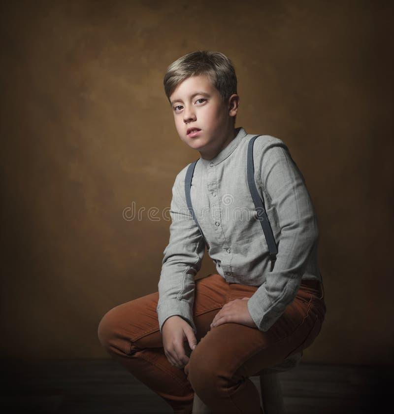 Portrait classique d'un garçon sur un fond orange-foncé photographie stock