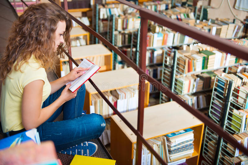 Portrait of clever student with book. S in college library stock photography