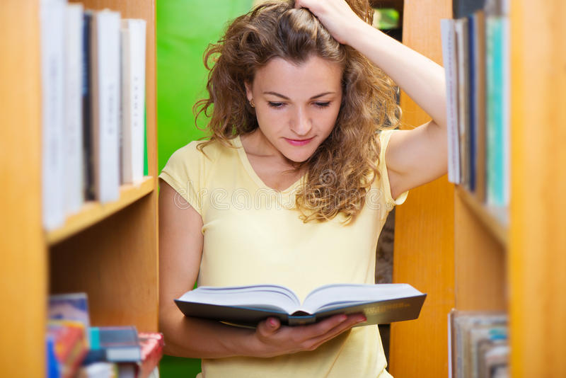 Portrait of clever student with book. S in college library royalty free stock photos