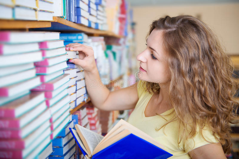 Portrait of clever student with book. S in college library royalty free stock image