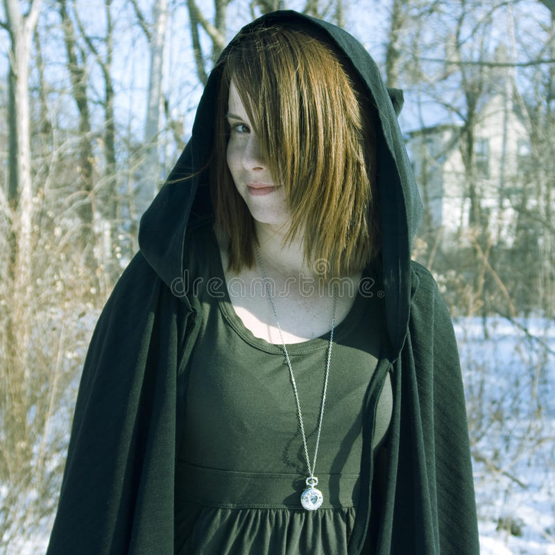 Portrait of a Cloaked Young Woman. A digitally cross-processed portrait of a young redheaded woman with a long necklace and a black hooded cloak royalty free stock image