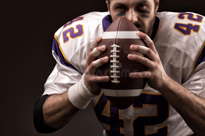 Portrait close-up, American football player, bearded without a helmet with the ball in his hands. Concept American royalty free stock photography