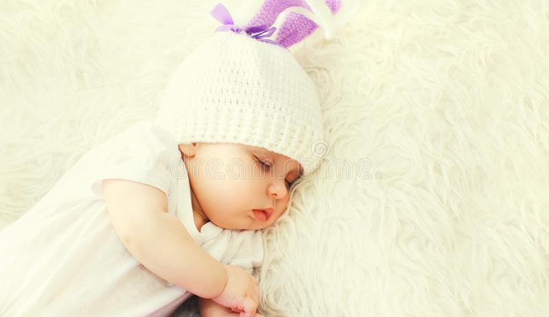 Portrait close-up baby sleeping in white knitted hat at home on bed royalty free stock image