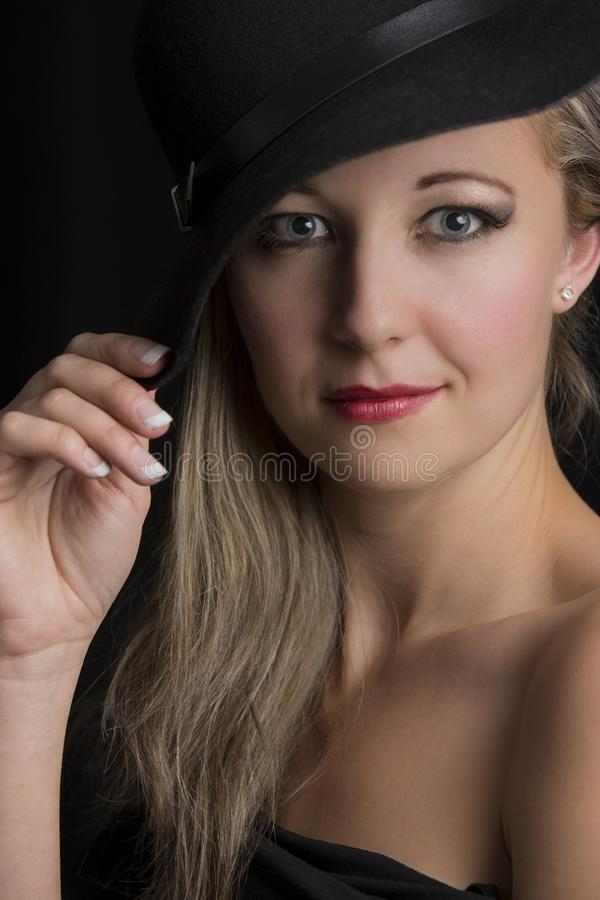 Portrait close-up of a beautiful blond woman with black hat stock images