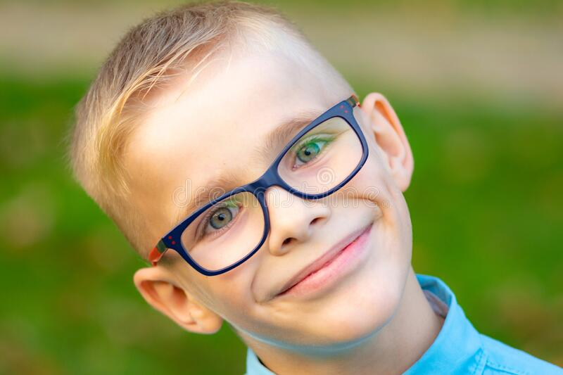 Portrait of a close-up of a cheerful boy with glasses stock photo