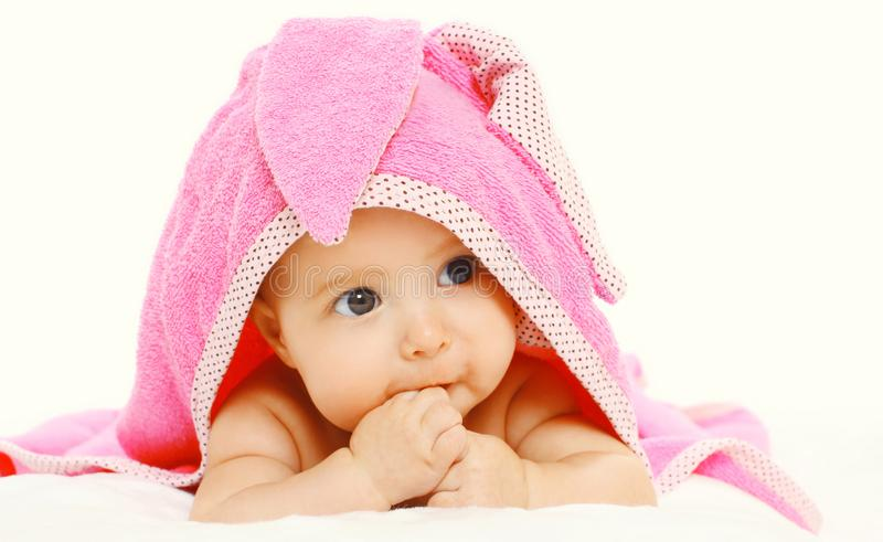 Portrait close-up cute baby under pink towel lying on bed isolated on white stock photos