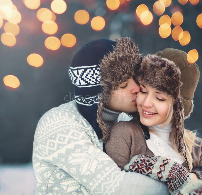 Portrait close-up happy couple in winter day, man gentle kissing woman in hat, knitted sweater, stock images
