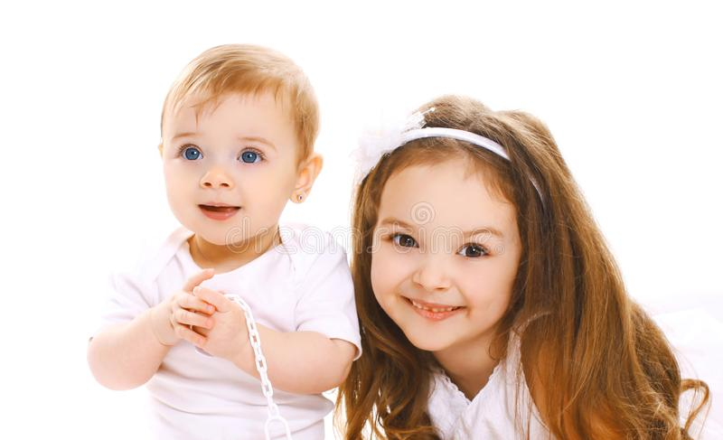 Portrait close-up happy smiling two children, older and younger sister isolated on white stock image