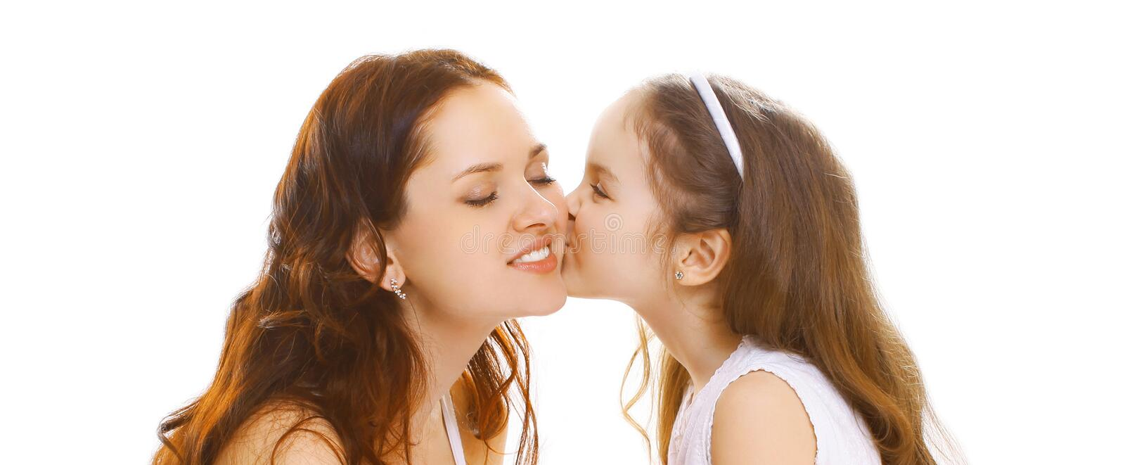 Portrait close-up little child daughter gently kissing her happy mother on white royalty free stock photo