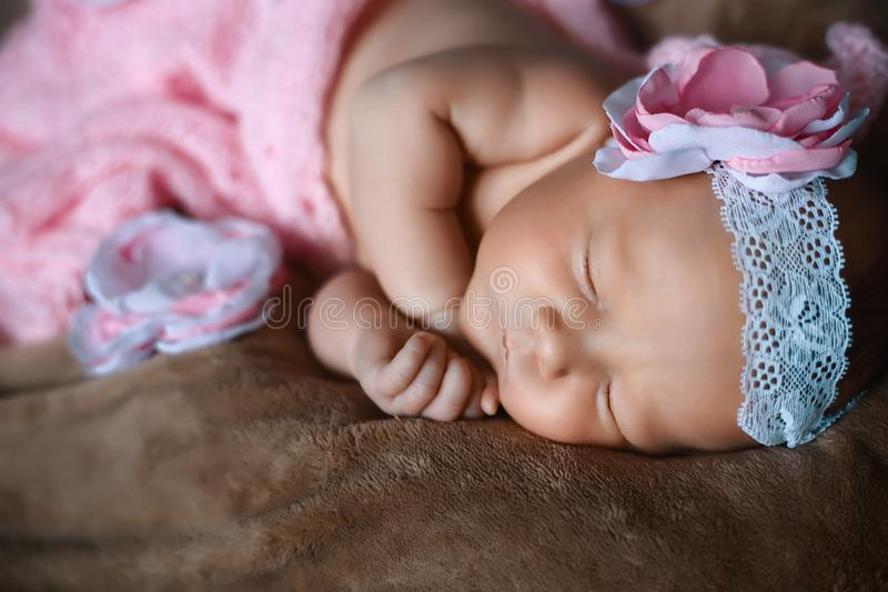 Portrait close-up newborn little girl who sleeps soap, soft pink scarf covered with lace satin flower stock photo