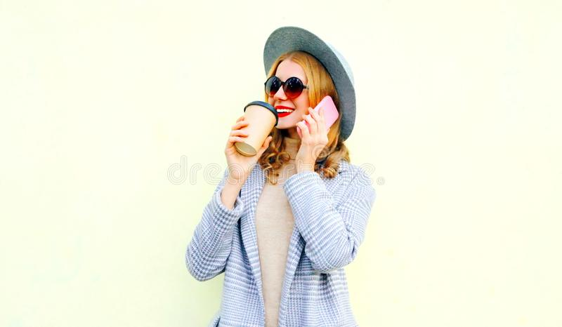 Portrait close-up smiling woman calling on smartphone on city street, wearing coat jacket. Round hat on background stock images