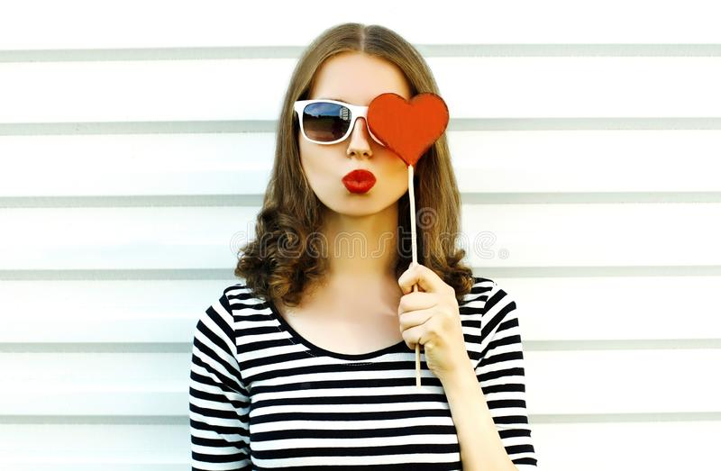 Portrait close-up woman blowing red lips sending sweet air kiss hiding her eye with red heart shaped lollipop on white wall royalty free stock photo
