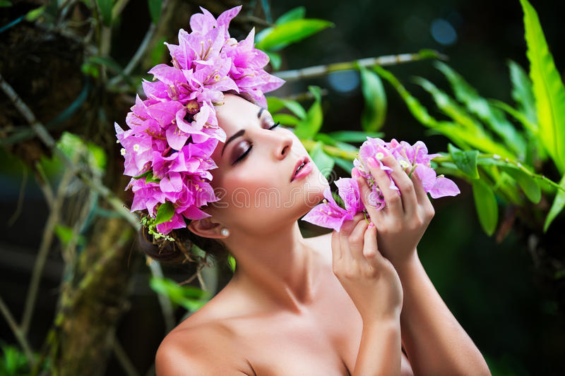 Portrait closeup of a beautiful young woman in a wreath of tropical flowers outdoor in the flowered garden royalty free stock image