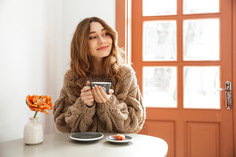 Portrait closeup of cute european woman sitting at table in cafe. Or restaurant and eating macaroons cakes with cup of tea royalty free stock images