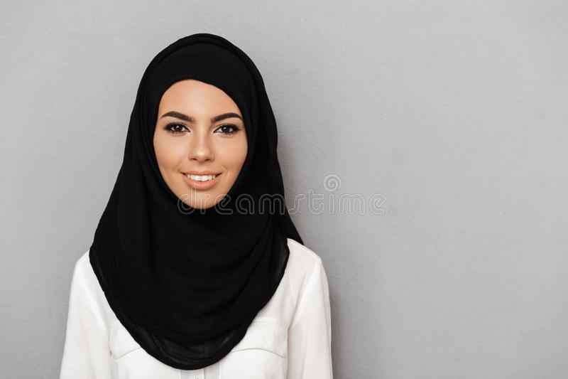 Portrait closeup of muslim prayer woman 20s in religious headscarf smiling and looking at camera, isolated over gray background stock images