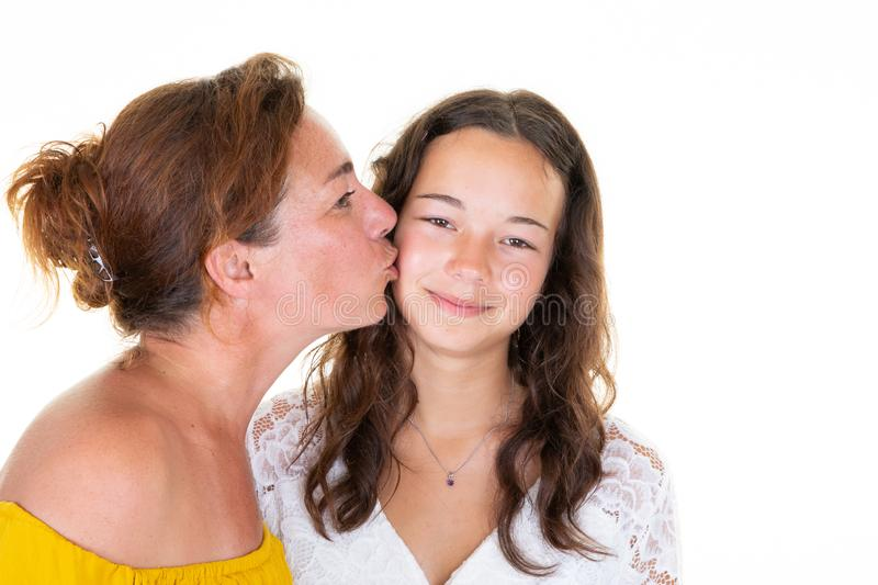 Portrait closeup two caucasian lovely women adult mother kissing on cheek her teenage daughter girl over white background royalty free stock photos