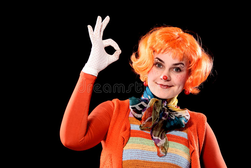 Portrait of clown. Youyng girl in a clown suit showing Ok stock image